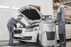 Αρσενικοί αυτοκινητικοί μηχανικοί που εξετάζουν το αυτοκίνητο στο κατάστημα επισκευής στοκ εικόνες με δικαίωμα ελεύθερης χρήσης
