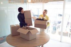 Αρσενικοί και θηλυκοί ανώτεροι υπάλληλοι που κρατούν τα κουτιά από χαρτόνι στην αρχή στοκ φωτογραφίες