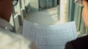 Αρσενικοί και θηλυκοί εκτελεστικοί μηχανικοί στα σκληρά καπέλα που περπατούν γύρω από το εργαστήριο εργοστασίων και που συζητούν  φιλμ μικρού μήκους