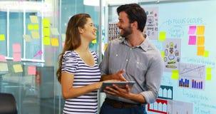 Αρσενικοί και θηλυκοί ανώτεροι υπάλληλοι που συζητούν πέρα από την ψηφιακή ταμπλέτα φιλμ μικρού μήκους