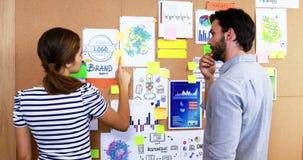 Αρσενικοί και θηλυκοί ανώτεροι υπάλληλοι που συζητούν πέρα από τον πίνακα δελτίων φιλμ μικρού μήκους