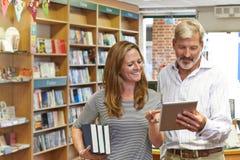 Αρσενικοί και θηλυκοί ιδιοκτήτες του βιβλιοπωλείου που χρησιμοποιεί την ψηφιακή ταμπλέτα στοκ φωτογραφία με δικαίωμα ελεύθερης χρήσης