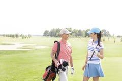 Αρσενικοί και θηλυκοί παίκτες γκολφ που επικοινωνούν στο γήπεδο του γκολφ Στοκ Εικόνες