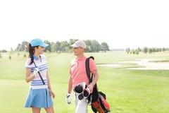 Αρσενικοί και θηλυκοί παίκτες γκολφ που επικοινωνούν στο γήπεδο του γκολφ Στοκ φωτογραφίες με δικαίωμα ελεύθερης χρήσης