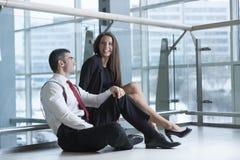 Αρσενικοί και θηλυκοί συνάδελφοι που κάθονται και που αστειεύονται από κοινού Στοκ φωτογραφίες με δικαίωμα ελεύθερης χρήσης