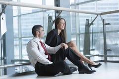 Αρσενικοί και θηλυκοί συνάδελφοι που κάθονται και που αστειεύονται από κοινού Στοκ Φωτογραφία