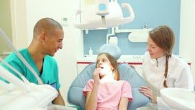 αρσενικοί οδοντικοί διαγωνισμοί χειρούργων χαριτωμένοι λίγος ασθενής με τον πονόδοντο απόθεμα βίντεο