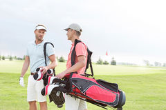 Αρσενικοί παίκτες γκολφ που επικοινωνούν στο γήπεδο του γκολφ ενάντια στο σαφή ουρανό Στοκ φωτογραφίες με δικαίωμα ελεύθερης χρήσης