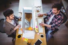 Αρσενικοί συνάδελφοι που χαμογελούν εργαζόμενοι στο γραφείο υπολογιστών Στοκ φωτογραφίες με δικαίωμα ελεύθερης χρήσης