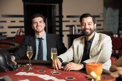 Αρσενικοί φίλοι που έχουν τη διασκέδαση σε μια χαρτοπαικτική λέσχη στοκ φωτογραφία