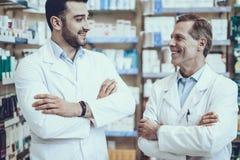 Αρσενικοί φαρμακοποιοί που θέτουν στο φαρμακείο στοκ φωτογραφίες