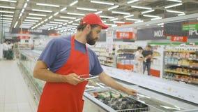 Αρσενικός έμπορος στα κόκκινα ομοιόμορφα προϊόντα ελέγχου με την ψηφιακή ταμπλέτα απόθεμα βίντεο
