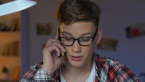 Αρσενικός έφηβος eyeglasses που μιλούν στο smartphone στο σπίτι, επικοινωνία συσκευών φιλμ μικρού μήκους