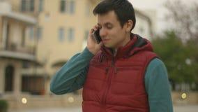 Αρσενικός αγγελιαφόρος που καλεί έναν πελάτη, ευτυχής νεαρός άνδρας που μιλά στο φίλο πέρα από το τηλέφωνο απόθεμα βίντεο