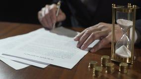 Αρσενικός αγοραστής ή πωλητής που υπογράφει τη συμφωνία αγορών, τα χρήματα και την κλεψύδρα στον πίνακα απόθεμα βίντεο