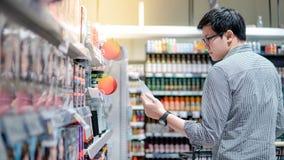 Αρσενικός αγοραστής που επιλέγει το πήκτωμα τρίχας στην υπεραγορά στοκ φωτογραφία με δικαίωμα ελεύθερης χρήσης