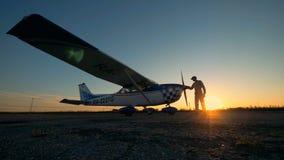 Αρσενικός αεροπόρος που καθαρίζει ένα αεροπλάνο σε ένα υπόβαθρο ηλιοβασιλέματος, πλάγια όψη απόθεμα βίντεο