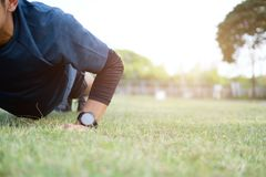 Αρσενικός αθλητής που ασκεί την ώθηση επάνω στο εξωτερικό στην ηλιόλουστη ηλιοφάνεια Στοκ Εικόνες