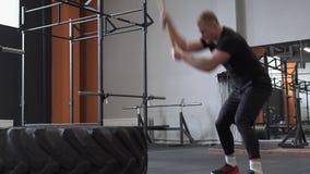 Αρσενικός αθλητής που κάνει την άσκηση ταλάντευσης βαρειών στη διαγώνια κατάλληλη γυμναστική απόθεμα βίντεο