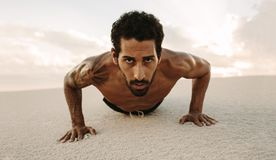 Αρσενικός αθλητής που κάνει την ώθηση UPS στην άμμο ερήμων στοκ φωτογραφία