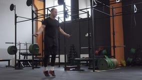 Αρσενικός αθλητής που κάνει το διπλό σχοινί αλμάτων στη διαγώνια κατάλληλη γυμναστική απόθεμα βίντεο