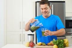 Αρσενικός αθλητής που κάνει το χυμό ή το καταφερτζή στην κουζίνα Στοκ Φωτογραφία