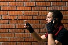 Αρσενικός αθλητικός τύπος που μιλά στο τηλέφωνο ασκώντας σε ένα κόκκινο υπόβαθρο τοίχων πετρών Στοκ Εικόνες