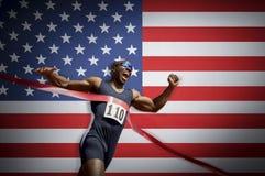 Αρσενικός αθλητής που διασχίζει τη γραμμή τερματισμού ενάντια στη αμερικανική σημαία Στοκ εικόνα με δικαίωμα ελεύθερης χρήσης