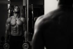Αρσενικός αθλητής που κάνει τη βαρέων βαρών άσκηση για τους δικέφαλους μυς Στοκ φωτογραφία με δικαίωμα ελεύθερης χρήσης