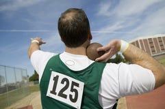 Αρσενικός αθλητής που προετοιμάζεται να ρίξει τον πυροβολισμό που τίθεται Στοκ Φωτογραφίες