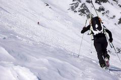 Αρσενικός ακραίος τίτλος σκιέρ προς μια υψηλή αλπική αιχμή βουνών στοκ εικόνες με δικαίωμα ελεύθερης χρήσης