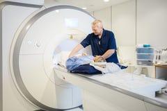 Αρσενικός ακτινολόγος που προετοιμάζει τη νέα γυναίκα για την ανίχνευση MRI Στοκ φωτογραφίες με δικαίωμα ελεύθερης χρήσης