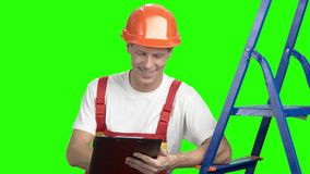 Αρσενικός ανάδοχος που γράφει στην περιοχή αποκομμάτων, πράσινη οθόνη απόθεμα βίντεο