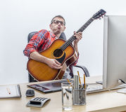 Αρσενικός ανεξάρτητος διασκέδασης που απολαμβάνει παίζοντας την κιθάρα στο γραφείο υπολογιστών του Στοκ εικόνες με δικαίωμα ελεύθερης χρήσης