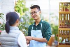 Αρσενικός ανθοκόμος που μιλά στον πελάτη του στο κατάστημα στοκ φωτογραφία