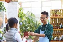 Αρσενικός ανθοκόμος που μιλά στον πελάτη του στο κατάστημα στοκ φωτογραφίες