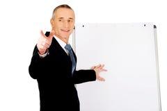 Αρσενικός ανώτερος υπάλληλος με το δείκτη που δείχνει σε κάποιο Στοκ Φωτογραφία