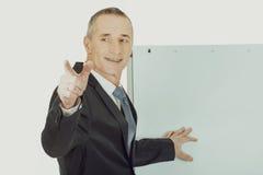 Αρσενικός ανώτερος υπάλληλος με το δείκτη που δείχνει σε κάποιο Στοκ Εικόνες