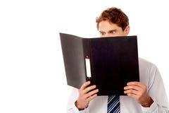 Αρσενικός ανώτερος υπάλληλος που αναθεωρεί τα έγγραφα επιχείρησής του Στοκ εικόνα με δικαίωμα ελεύθερης χρήσης