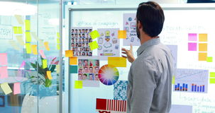 Αρσενικός ανώτερος υπάλληλος που εξετάζει τις κολλώδεις σημειώσεις για το whiteboard απόθεμα βίντεο