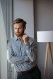 Αρσενικός ανώτερος υπάλληλος που κοιτάζει μέσω του παραθύρου στην αρχή Στοκ Εικόνα