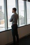 Αρσενικός ανώτερος υπάλληλος που κοιτάζει μέσω του παραθύρου στην αρχή Στοκ φωτογραφία με δικαίωμα ελεύθερης χρήσης