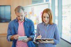 Αρσενικός ανώτερος υπάλληλος που χρησιμοποιεί την ψηφιακή ταμπλέτα ενώ θηλυκός ανώτερος υπάλληλος που σημειώνει στο ημερολόγιο Στοκ εικόνες με δικαίωμα ελεύθερης χρήσης