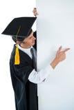 Αρσενικός απόφοιτος φοιτητής πίσω από μια επιτροπή και υπόδειξη με το δάχτυλο Στοκ Φωτογραφίες