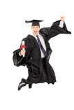 Αρσενικός απόφοιτος φοιτητής που πηδά από τη χαρά Στοκ Φωτογραφία