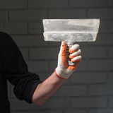 Αρσενικός αριστερός βραχίονας στο γάντι που κρατά το μεγάλο μαύρο βρώμικο κατασκευασμένο putty μαχαίρι σε μια ευρεία αφηρημένη γρ Στοκ Εικόνες