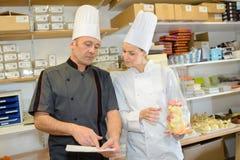Αρσενικός αρχιμάγειρας πορτρέτου με τη γυναίκα βοηθός στην κουζίνα Στοκ Εικόνες