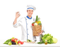 Αρσενικός αρχιμάγειρας που κρατά ένα σύνολο τσαντών του υγιούς φυτικού ΝΕ ingridients Στοκ Φωτογραφίες