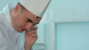 Αρσενικός αρχιμάγειρας στο άσπρο ομοιόμορφο μαγείρεμα και την ομιλία στο τηλέφωνο απόθεμα βίντεο