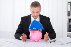 Αρσενικός αρχιτέκτονας με Piggybank που φορά το κράνος κατασκευής Στοκ φωτογραφία με δικαίωμα ελεύθερης χρήσης
